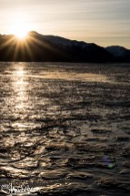 The sun breaks over the plane of the mountains at Kluane Lake.