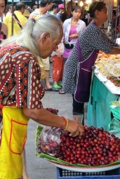 Old lady picking out her cherries