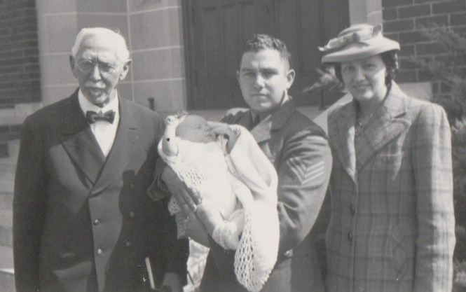 Carl Wagner holds his son 'Ted' on the aby's christening day