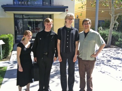 A portait of four musicians in front of a concert hall.