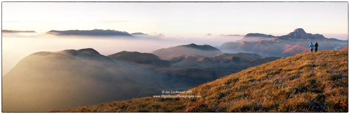 """Looking south over the 2,000 meter high Eravikulam plateau from Kattu Malai. The sunrise highlights the extensive """"downs"""" of the shola/grasslands complex that is uniquely preserved in this magical National Park. Anai Mudi's distinctive hat profile is on the right horizon while the edges of the Palalni Hills are on the far left. My father Merrick and cousin Anna are at the edge taking in an unforgettable Western Ghats experience."""