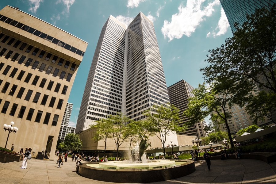 An exterior photo of Place Ville Marie (PVM for short), a large office and shopping complex in central Montreal, Quebec, Canada, comprising four office buildings and an underground shopping plaza. The main building, 1 Place Ville Marie (formerly Royal Bank Tower from its anchor tenant), built in the International style in 1962 as headquarters for the Royal Bank of Canada, is arguably the city's most distinctive building: a 188 m (617 ft), 47-storey, cruciform office tower. The complex is a nexus for Montreal's Underground City, the world's busiest, with indoor access to over 1,600 businesses, several subway stations, a suburban transportation terminal, and tunnels extending throughout downtown. A counter-clockwise rotating beacon on the rooftop lights up at night, illuminating the surrounding sky with up to four white horizontal beams that can be seen as far as 50 km away.
