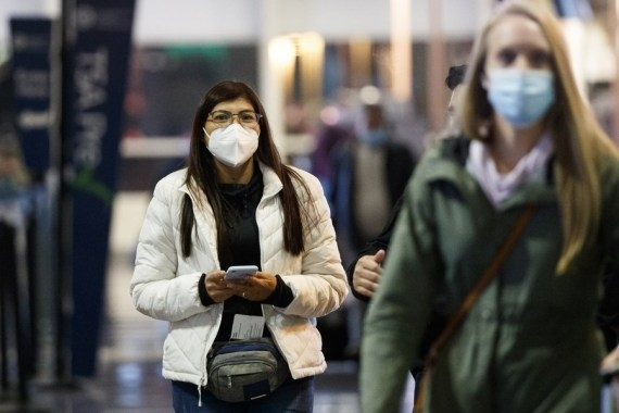 People wearing face masks are seen at Ronald Reagan Washington National Airport in Arlington, Virginia, the United States, on Dec. 23, 2020. (Photo by Ting Shen/Xinhua/ians)