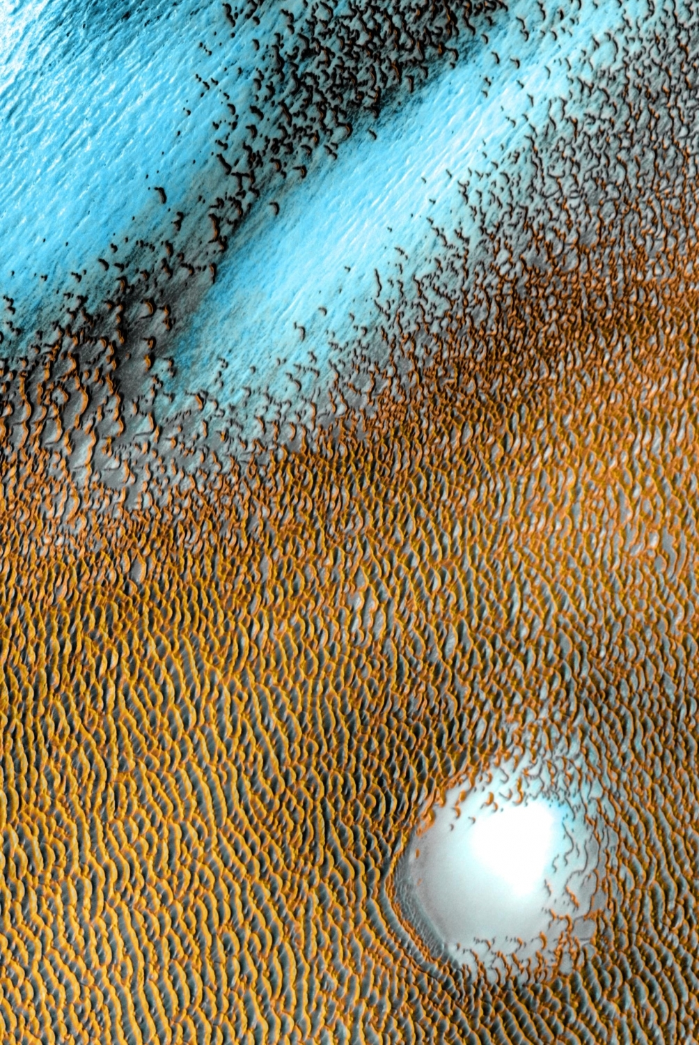 Pictures taken between 2002 and 2004 by Odyssey's THEMIS imager up this wind-sculpted sea of dark dunes that covers an area as big as Texas at Mars' northern polar cap. In this enhanced-colour image, cooler areas have in bluer tints, while warmer features are depicted in yellows and oranges. Photo: NASA/JPL-Caltech/ASU