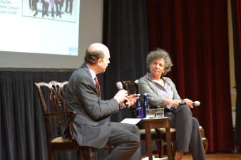 On a stage, a man in a suit holding a microphone interviews a woman.