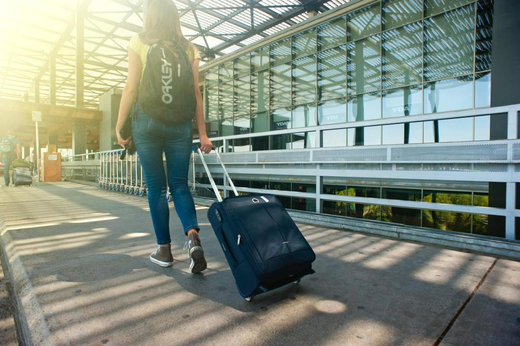 A girl walking through the airport with travelers insurance