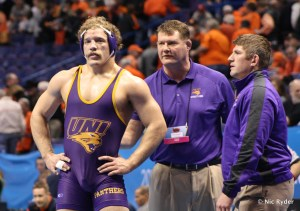UNI Assistant Coach Tolly Thompson talks to heavyweight Blaize Cabell before a match at the 2015 NCAA Championship