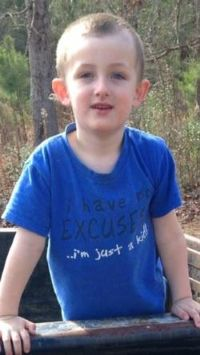 Photo of a boy with short blond hair and pale skin, photographed outdoors; he is wearing a blue T-shirt that says, I have no excuse... I'm just a kid!