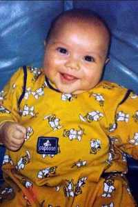 Baby photo of Julian Pintar, a chubby infant in a yellow romper.