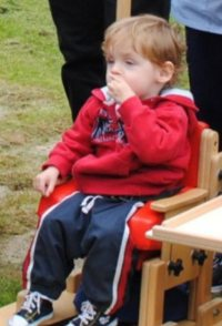 Photo of Leylan Forte. He is a toddler with very light skin and dark blond hair, wearing sweatpants and a hoodie. He is sitting in a wood and red plastic chair.