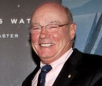 Photo of Richard Oland. He is an elderly bald man with fair skin. He is wearing a suit, black tie, and glasses.