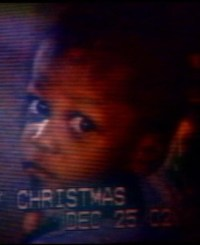 Photo of a TV screen. On the screen is a small African-American boy with a solemn expression on his face.
