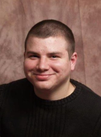 Portrait photo of Ryan Birse. He is a young man with light skin and dark brown hair in a buzz cut. He is wearing a black sweater.