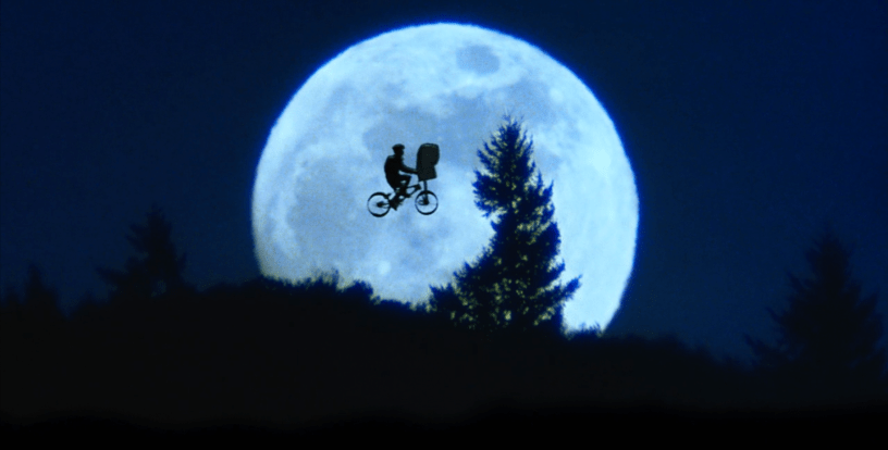 Elliott (Henry Thomas) and E.T. fly a bike across the moon in an iconic shot from E.T. THE EXTRA-TERRESTRIAL (1982)