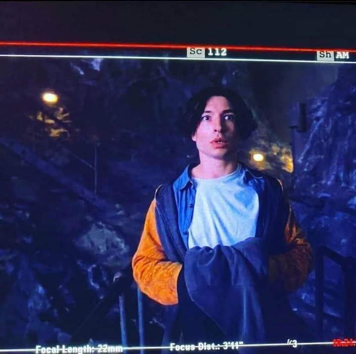 Ezra Miller stars as Barry Allen (The Flash) in THE FLASH (2022). Here, as seen from a monitor on-set during filming, Barry sees The Batcave for the first time.