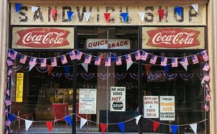 A sandwich shop in 1969 NYC, decorated on a ticker tape parade route for the Apollo 11 crew in INDY 5.