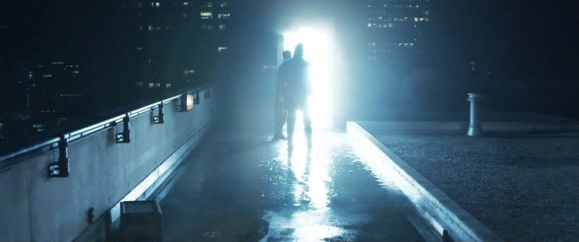 Neo (Keanu Reeves) is led through a portal in THE MATRIX RESURRECTIONS (2021)