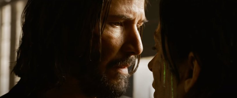 Neo and Trinity (Keanu Reeves and Carrie-Anne Moss) meet for the first time, again, in Neo fights off attackers and bullets in THE MATRIX RESURRECTIONS (2021)