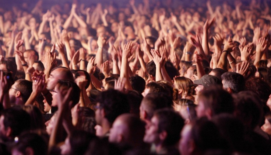 Image of group of people at an event raising their hands up cheering
