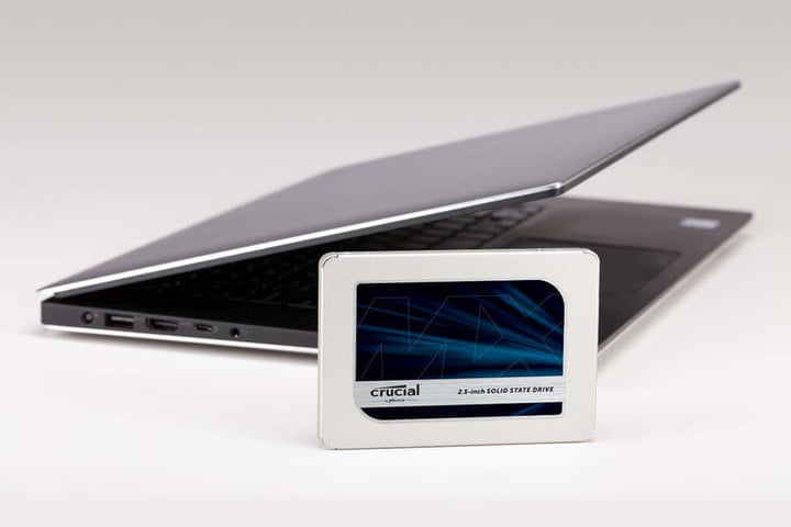 Crucial MX500 SSD in front of a laptop.