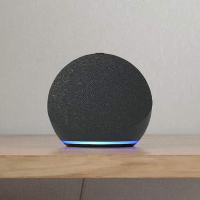 Amazon Echo Dot (4th Gen) in Charcoal with eyeglasses nearby.