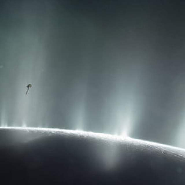 An artist's impression depicts NASA's Cassini spacecraft flying through a plume of presumed water erupting from the surface of Saturn's moon Enceladus.