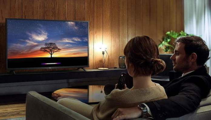 Man and woman are watching TV on the sofa.