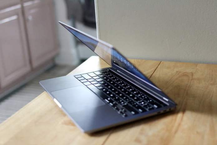 A MacBook Pro viewed from the side, with its lid partially closed.