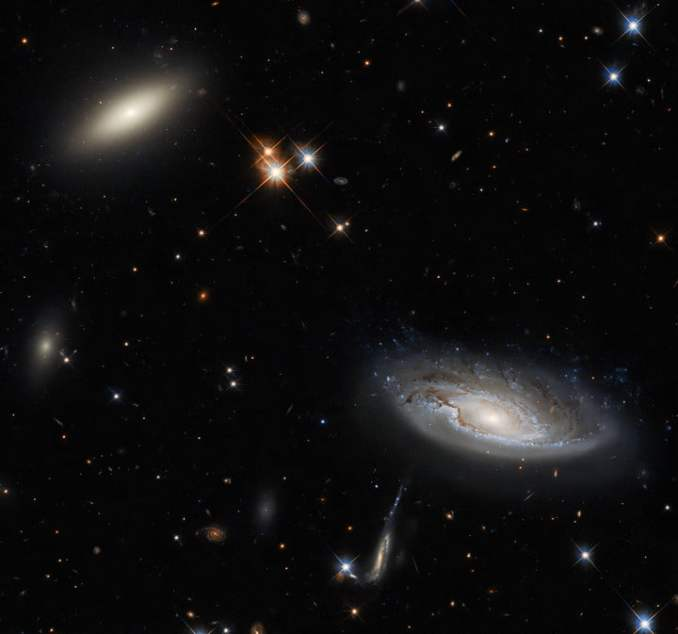 Two enormous galaxies shine. The galaxy on the left is a lenticular galaxy, named 2MASX J03193743+4137580. The side-on spiral galaxy on the right is named UGC 2665.