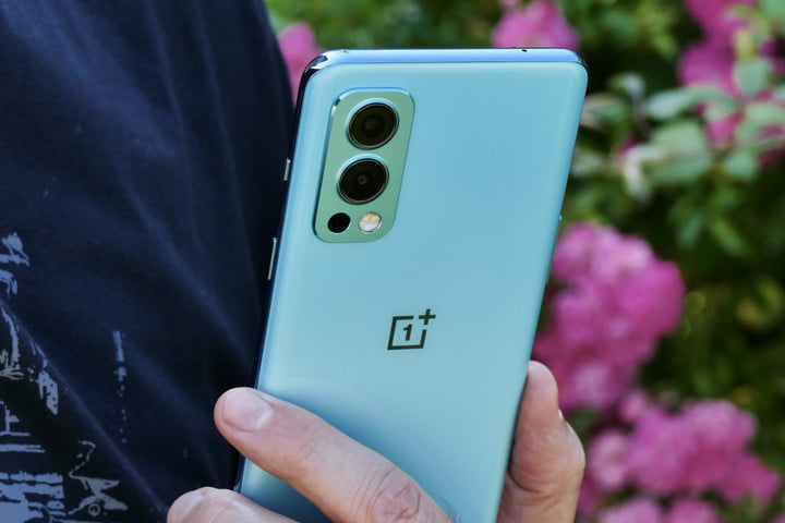 The OnePlus Nord 2 held in hand, seen from the back.