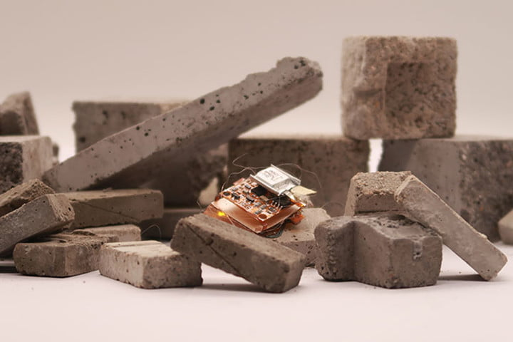 A tiny insect-sized robot is maneuvering over uneven blocks of stone.