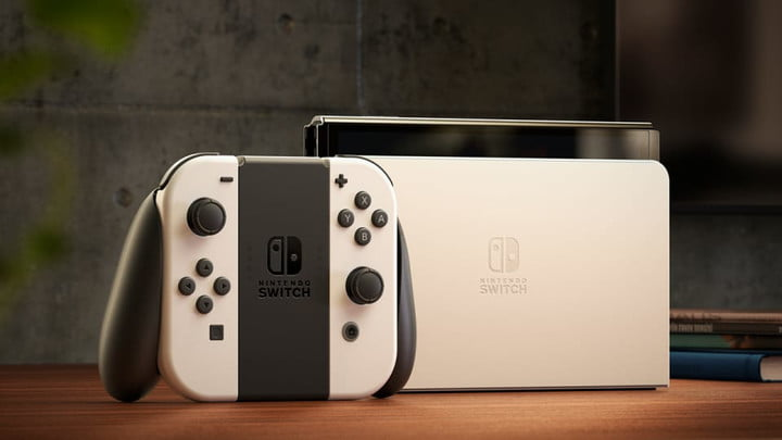 White Nintendo Switch OLED in dock with Joy-Con in grip.