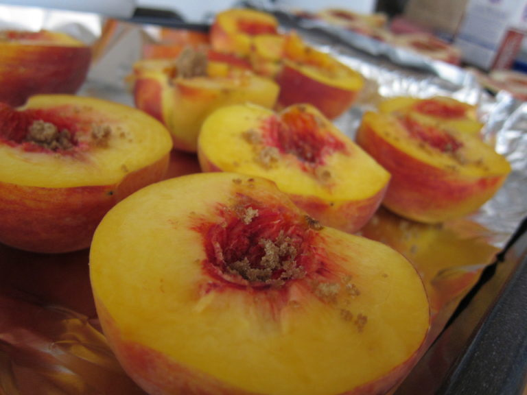 Peaches topped with brown sugar ready to be roasted