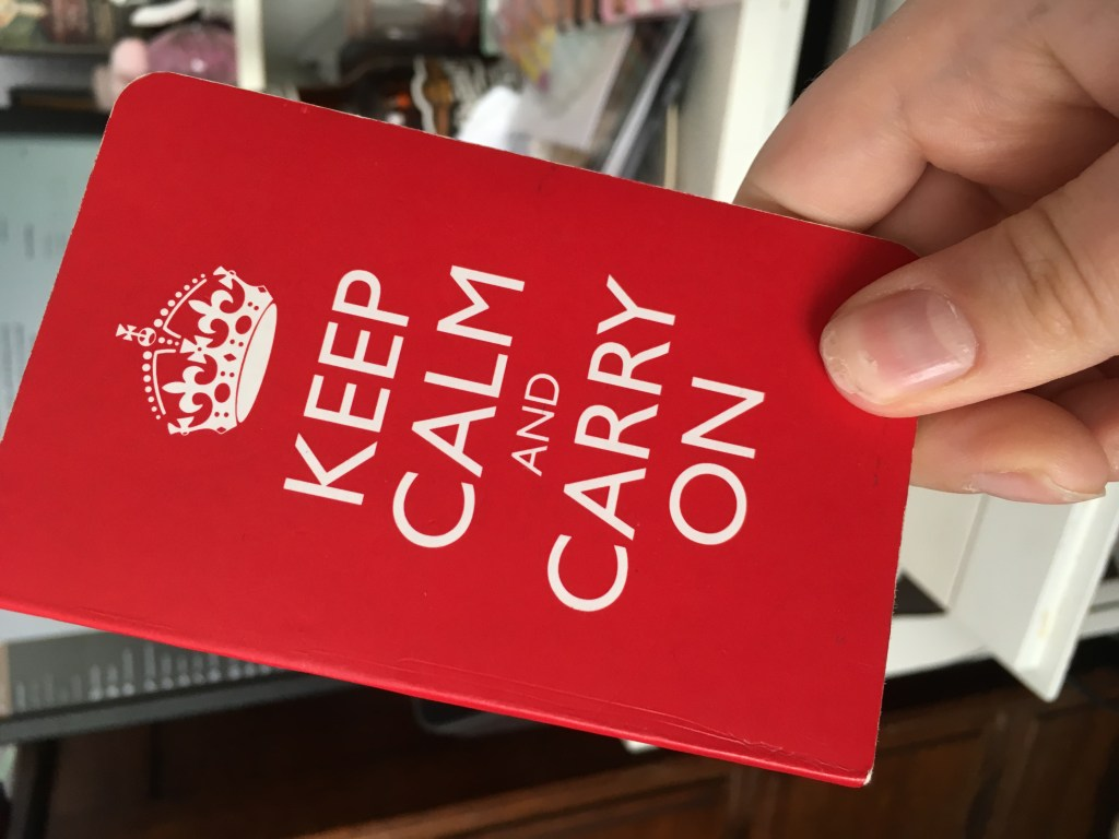 "A picture of me holding up my tiny pocket notebook that's got ""Keep Calm and Carry On"" written on the cover."