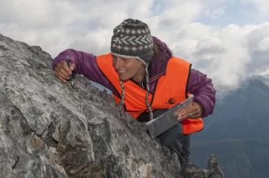 """Sonja Wipf (Forschungsgruppe Gebirgsökosysteme SLF und Mitautorin der Studie) bei Pflanzen-Aufnahmen auf dem Piz Murter im Schweizer Nationalpark (Engadin, GR). Oben am Fels hat sie noch ein kleines """"Hungerblümchen"""" (Draba aizoides) entdeckt. Bild: Schweizerischer Nationalpark/Hans Lozza"""
