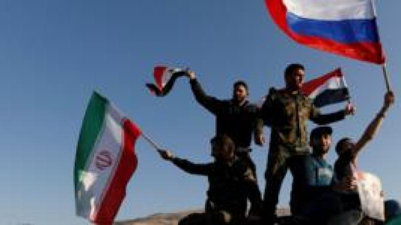 Syrians wave Iranian, Russian and Syrian flags during a protest against U.S.-led air strikes in Damascus,Syria April 14,2018.