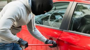 Burglar breaking into car