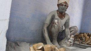 Worker Narayanswamy with polythene covering his head hammering explosive powder into cones with body covered in aluminium powder