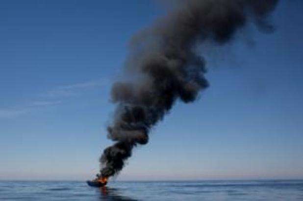 A small wooden boat used by refugees and migrants is seen burning after being set alight after all people were rescued by rescue crews from the Migrant Offshore Aid Station (MOAS) Phoenix vessel on 18 May 2017 in the Lampedusa, Italy.
