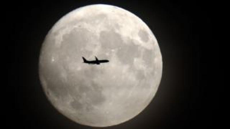 A plane flies in front of the Moon