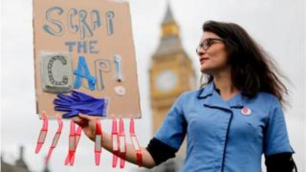 Demonstrators hold placards as they participate in a protest, organised by nurses, against the British government's pay cap on public sector workers