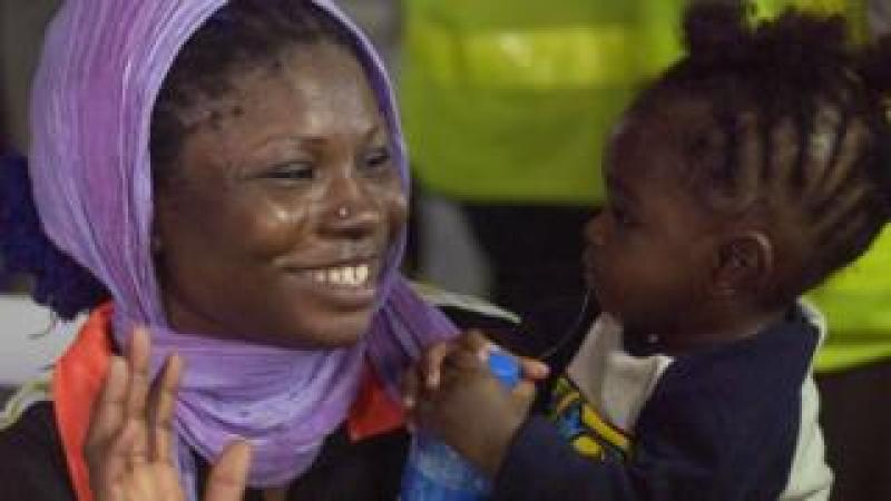 A woman plays with a child during the screening of 150 migrants brought home from Libya at the Murtala Mohammed International Airport in Lagos, Nigeria - Tuesday 5 December 2017