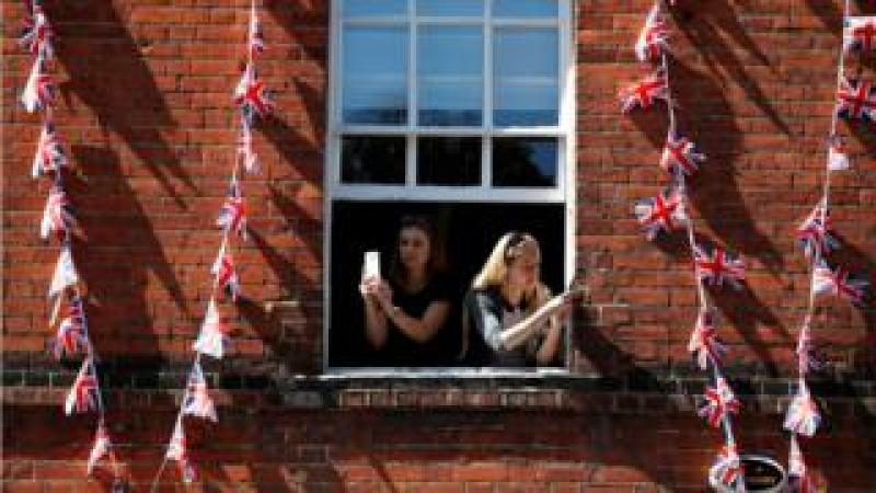 Women take photos on their smartphones as they lean out of the window of a building near Windsor Castle