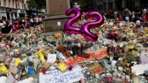 Balloons, flowers and messages of condolence are left for the victims