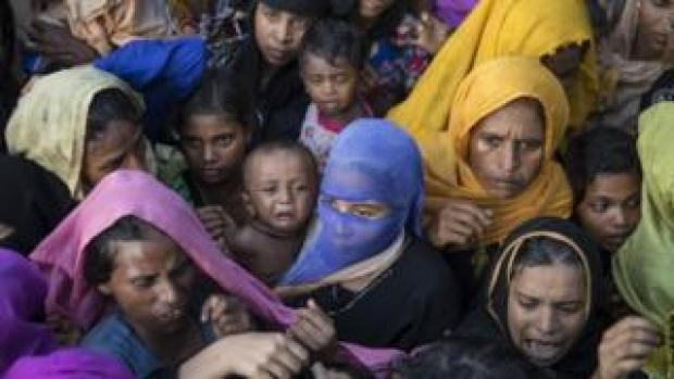 Rohingya reach out for clothing and food on 15 September 2017 in Tankhali, Bangladesh
