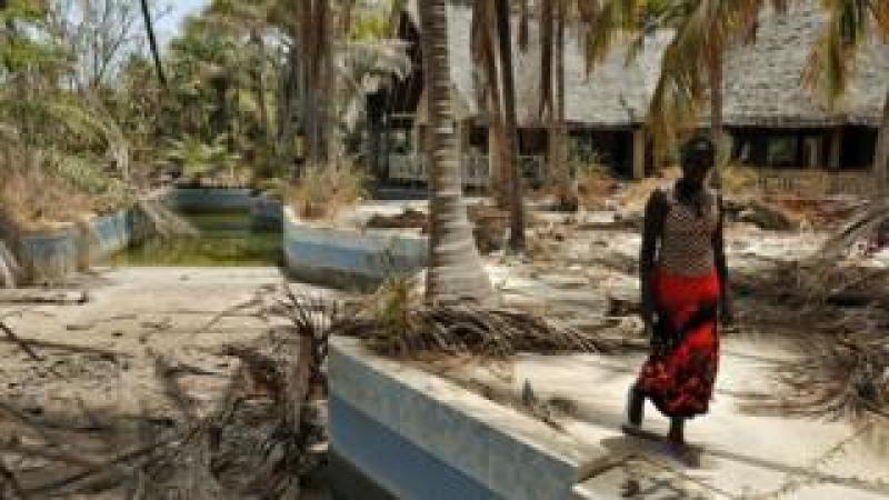 A Senegalese woman walks near an abandoned hotel