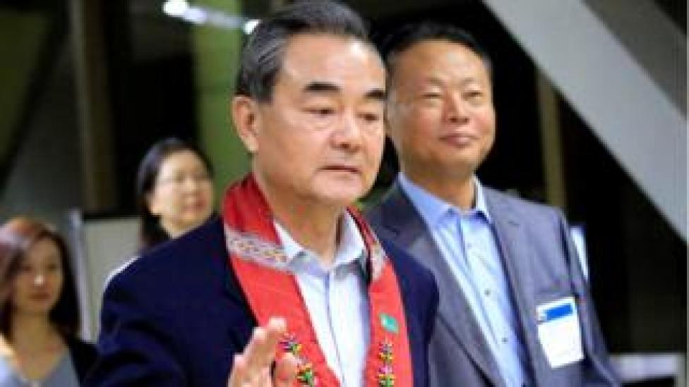 """People""""s Republic of China Foreign Minister Wang Yi gestures as he is escorted by Zhao Jianhua, Chinese ambassador to the Philippines, upon arrival at the international airport of Pasay to attend the 50th ASEAN Foreign Ministers meeting, metro Manila, Philippines August 5, 2017"""