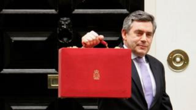 Britain's Chancellor of the Exchequer Gordon Brown holds a brief case holding the annual budget as he leaves No 11 (Number Eleven) Downing Street on March 22, 2006 in London England.