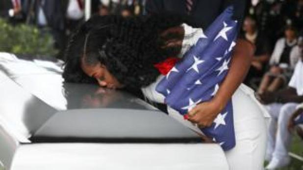 Myeshia Johnson weeping on her husband's coffin at his funeral in Hollywood, Florida on 21 October