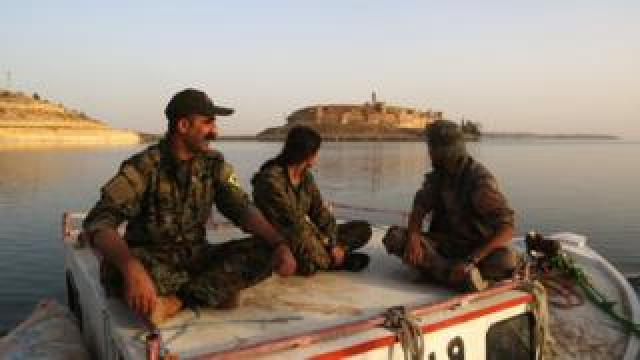 Members of the US-backed Syrian Democratic Forces look towards Jaabar Castle from a boat on Lake Assad, a reservoir created by the Tabqa dam. April 29, 2017